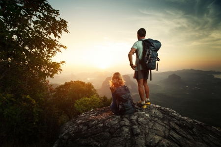 climbing mountain: Hikers with backpacks standing on top of a mountain and enjoying sunrise Stock Photo