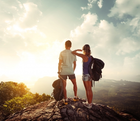 trek: Hikers with backpacks standing on top of a mountain and enjoying sunrise Stock Photo