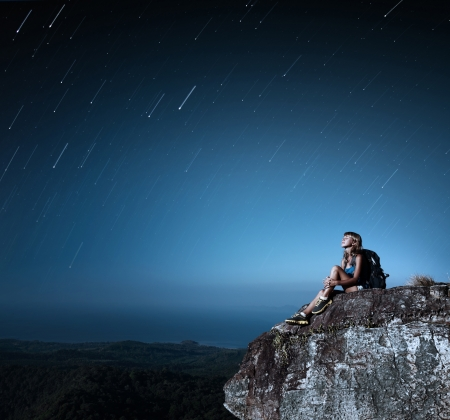 Tourist with backpack relaxing on top of a mountain at bright night with stars in a sky photo