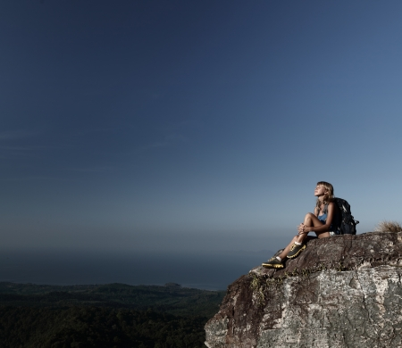 cliff edge: Young hiker relaxing on top of a mountain