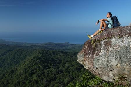 Caminante joven que se relaja en la cima de una montaña