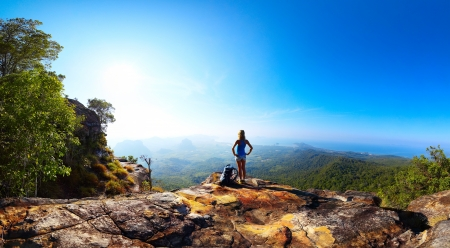 Hiker with backpack standing on top of a mountain and enjoying stunning valley view photo