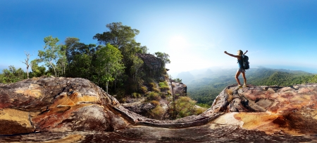 woman mountain: Hiker with backpack standing on top of a mountain with raised hands and enjoying stunning valley view Stock Photo