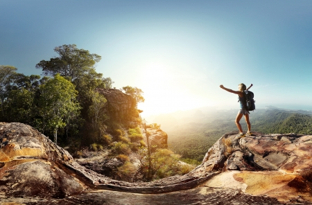 altitude: Hiker with backpack standing on top of a mountain with raised hands and enjoying sunrise Stock Photo