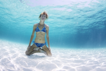 Young woman holding a breath and relaxing on a sandy bottom in a yogic lotus position Stock Photo - 19362644