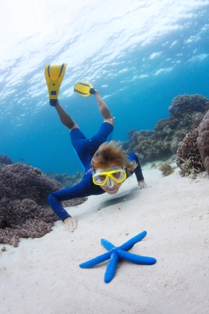 Young woman exploring sandy sea bottom and watching blue sea star photo