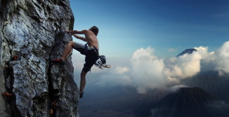 belay: Young man climbing natural rocky wall with volcanoes on the background Stock Photo