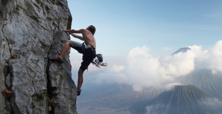 climbing mountain: Young man climbing natural rocky wall with volcanoes on the background Stock Photo
