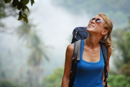 woman hiking: Young tourist with backpack walking in tropical forest Stock Photo