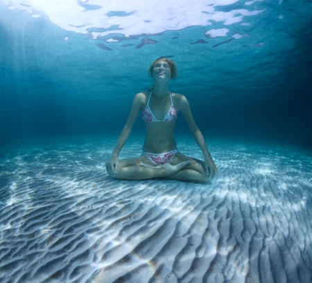 weightless: Young woman sitting on a sea sandy bottom in lotus position and holding a breath