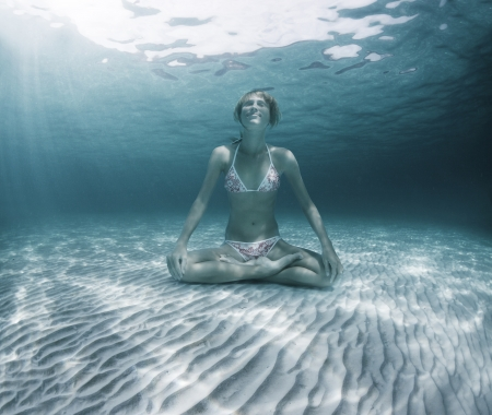 underwater sport: Young woman sitting on a sea sandy bottom in lotus position and holding a breath