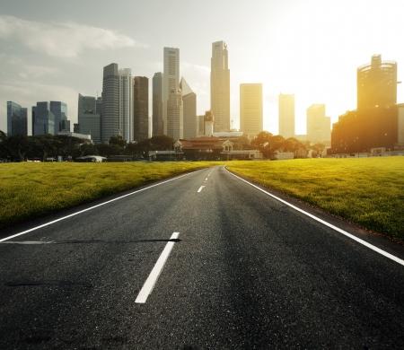 Asphaltstraße führt zu einer Stadt mit hohen Gebäuden durch grüne Wiese Standard-Bild