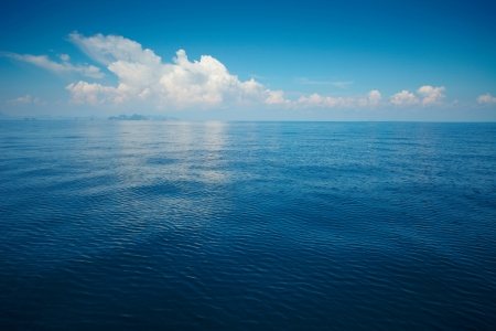 deep sea: Tropical rippled and calm sea with far islands on the horizon and white fluffy clouds Stock Photo