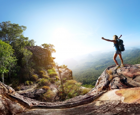 climbing: Hiker with backpack standing on top of a mountain with raised hands and enjoying sunrise Stock Photo