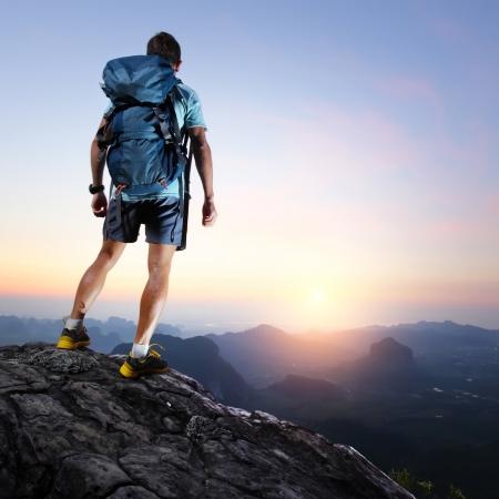 mochila: Caminante con mochila de pie en la cima de una monta�a y disfrutar de la salida del sol