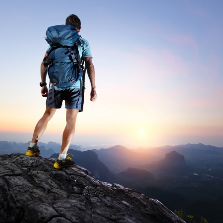 Hiker with backpack standing on top of a mountain and enjoying sunrise Stock Photo - 19362402