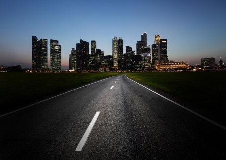 Asphalt road and a city with illuminated buildings on the horizon photo