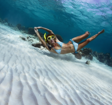 Young lady snorkeling in a transparent tropical sea over sandy bottom photo