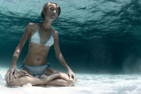 face work: Underwater portrait of a young lady holding a breath on a sandy bottom in a yogic lotus position Stock Photo