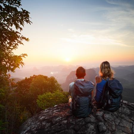 Jong koppel met rugzakken ontspannen op de top van een berg en genieten van uitzicht op de vallei tijdens zonsopgang