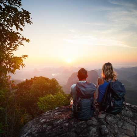 senderismo: Pareja joven con mochilas relajarse en la cima de una monta�a y disfrutar de vistas al valle durante el amanecer