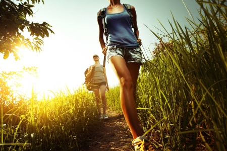 backpackers: Two young ladies walking with backpacks on a thin path through a lush tropical meadow