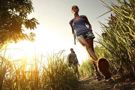 caminando: Dos mujeres j�venes con mochilas caminando por prado verde tropical