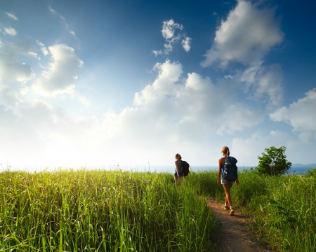 Hikers with backpacks walking through a meadow with lush grass Stock Photo