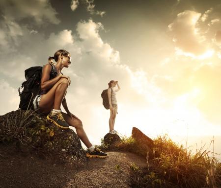 mochila: Dos turistas j�venes con mochilas de relax en las rocas y disfrutar de la puesta del sol Foto de archivo