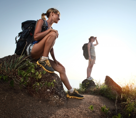Two young tourists with backpacks relaxing on rocks Stock Photo