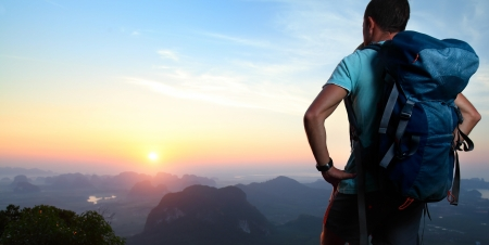 cross light: Hiker with backpack standing on top of a mountain and enjoying sunrise.