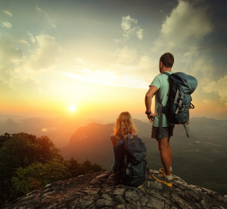Tourists with backpacks enjoying sunrise on top of a mountain Stock Photo