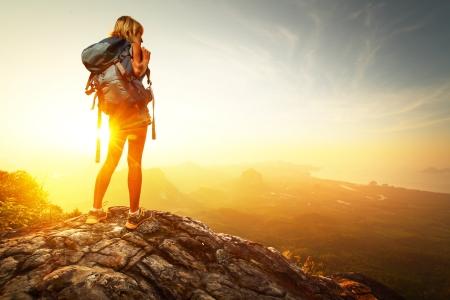 Caminante con mochila relajarse en la cima de una montaña y disfrutar de vistas al valle durante el amanecer