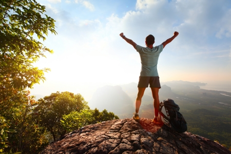 Hiker with backpack standing on top of a mountain with raised hands Stock Photo