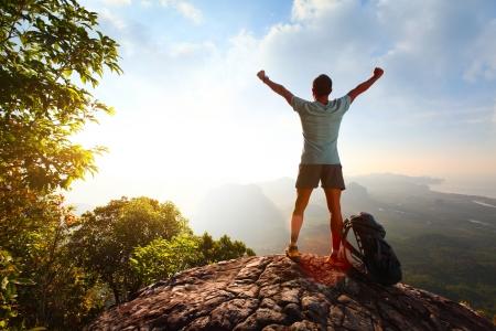 Wandelaar met rugzak staande op de top van een berg met opgeheven handen Stockfoto