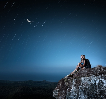 sky night: Tourist with backpack relaxing on top of a mountain at bright night with stars in a sky
