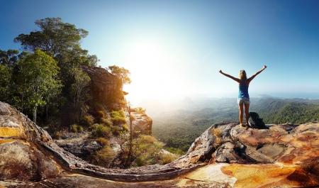 Caminante con mochila disfrutando de vistas al valle desde la cima de una montaña
