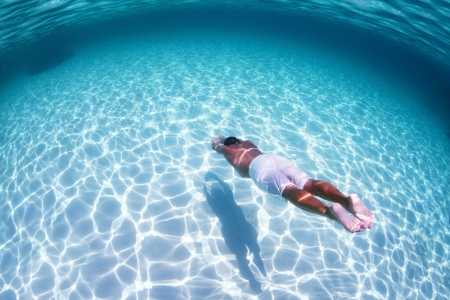 dive: Hombre de buceo joven en una retenci?n de la respiraci?n en un mar tropical sobre fondo de arena Foto de archivo