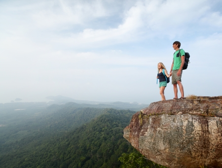 cliff edge: Two hikers standing on top of a mountain and enjoying valley view