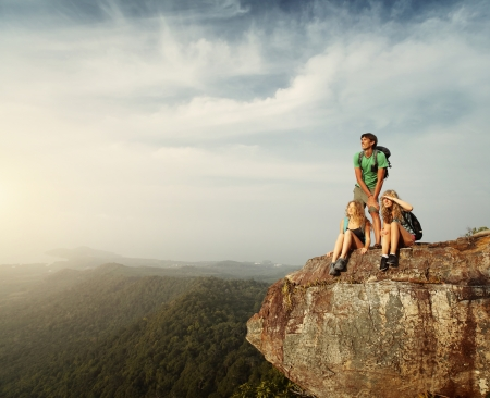 cliff edge: Group of young hikers relaxing on top of a mountain and enjoying sunrise