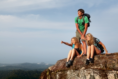 Group of young hikers relaxing on top of a mountain photo
