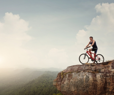 steep cliff: Young athlete standing on top of a mountain with bicycle and enjoying valley view