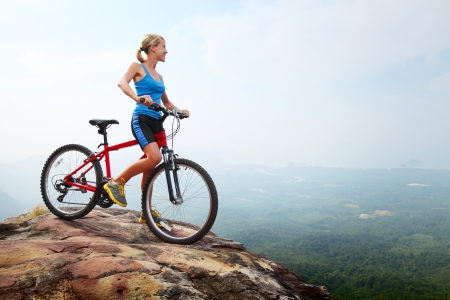 Young slim lady standing on top of a mountain with bicycle and enjoying valley view photo
