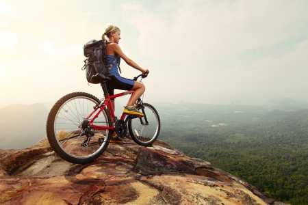 Young woman athlete standing on top of a mountain with red bicycle and enjoying valley view Stock Photo