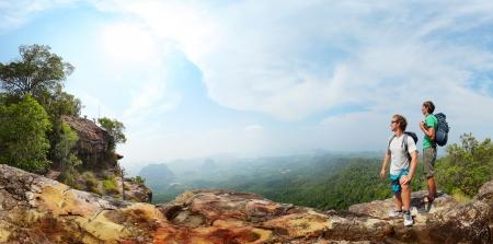 mochila: Panorama con dos mochileros masculinos de pie en la cima de una monta�a y mirando a un valle