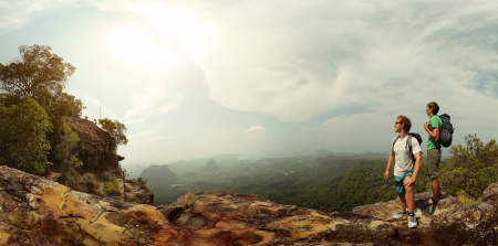 Panorama with two male backpackers standing on top of a mountain and looking to a valley photo