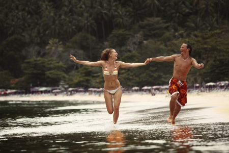 along: Young happy couple running together along a tropical beach Stock Photo