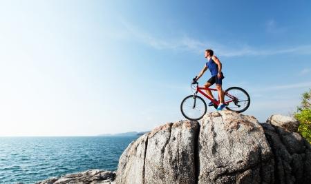 valley view: Giovane donna sottile in piedi sulla cima di una montagna con la bici e godersi la vista sulla valle