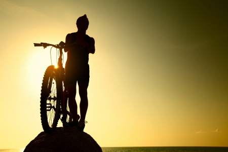 Young athlete standing on a rock with bicycle photo