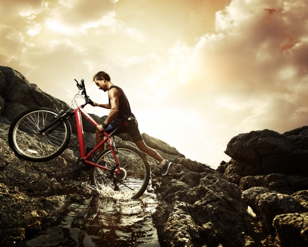 Young athlete crossing water barrier with bicycle photo